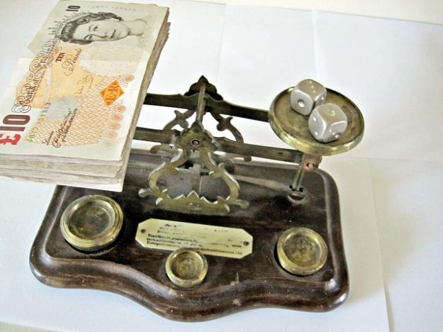 Money and dice on scales