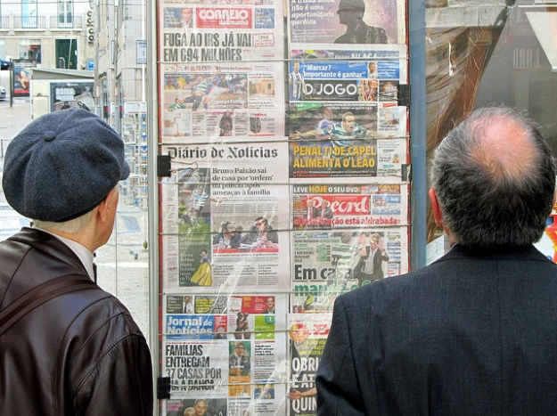 Two men scan the newspaper headlines