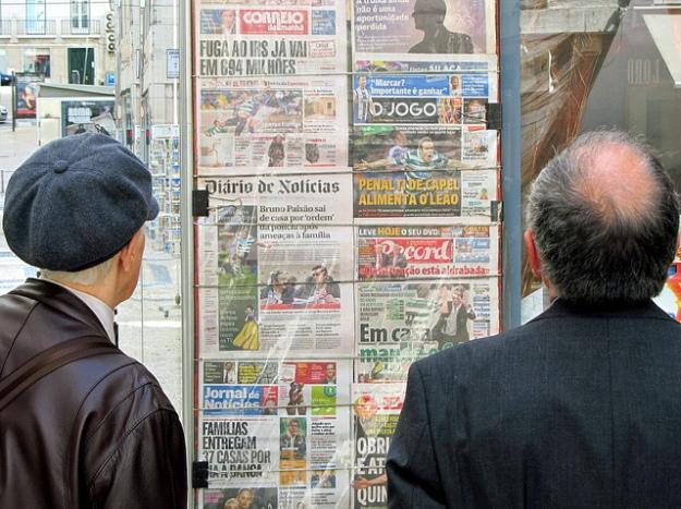 Two men scan the newspaper headlines