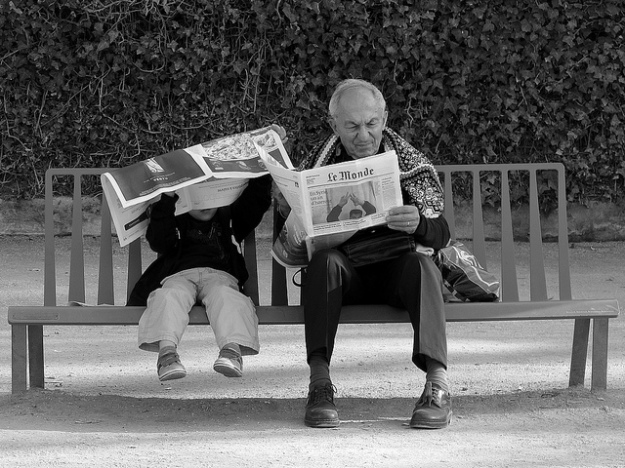 Old man and young boy reading on bench